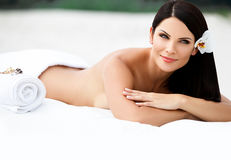 Ung kvinna som kopplar av på stranden efter massage. arkivbilder