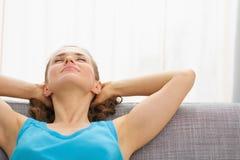 Ung kvinna som kopplar av på soffan i vardagsrum Arkivbilder