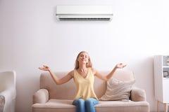 Ung kvinna som kopplar av under luftkonditioneringsapparaten arkivbild