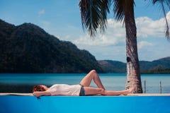 Ung kvinna som kopplar av vid simbassängen Royaltyfria Bilder