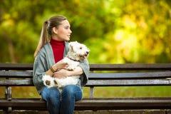 Ung kvinna som kramar en maltese hund Arkivbild