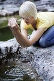 Ung kvinna som kuper vatten från en vaggapöl royaltyfria bilder