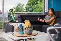 Ung kvinna som kyler på soffan som läser en ebook royaltyfri bild