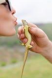 Ung kvinna som kysser en ödla royaltyfria bilder