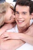 Ung kvinna som kysser henne pojkvän Arkivbilder