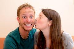 Ung kvinna som kysser henne pojkvän Arkivfoto