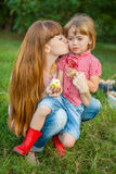 Ung kvinna som kysser hennes lilla dotter Royaltyfria Bilder