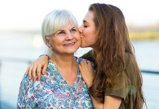 Ung kvinna som kysser hennes mormor royaltyfri foto