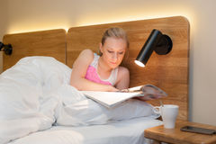 Ung kvinna som lägger i säng som läser en tidskrift Arkivfoto