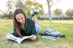 Ung kvinna som lägger i studera för gräs Fotografering för Bildbyråer