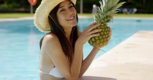 Ung kvinna som läppjar en ananascoctail arkivfilmer