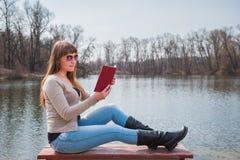 Ung kvinna som läser boken som är utomhus- i solglasögon, daglig livsstil, flod på bakgrunden, vår, solig dag Arkivfoton