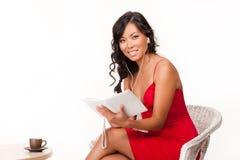 Ung kvinna som läser den elektroniska boken Arkivbilder