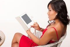 Ung kvinna som läser den elektroniska boken Royaltyfri Fotografi