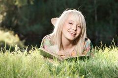 Ung kvinna som läser en bok Fotografering för Bildbyråer
