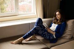 Ung kvinna som läser en bok bredvid ett fönster fotografering för bildbyråer