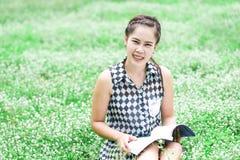 Ung kvinna som läser en bok i ängen Arkivbild