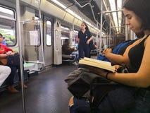 Ung kvinna som läser en bok, medan resa inom tunnelbanan av Medellin arkivfoto