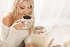 Ung kvinna som läser en bok och dricker kaffe arkivbilder