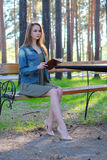 Ung kvinna som läser en bok och kopplar av på parkera arkivbilder