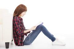 Ung kvinna som läser en bok och sitter på golvet Arkivfoto
