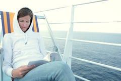 Ung kvinna som läser en bok på en eyeliner Arkivbilder
