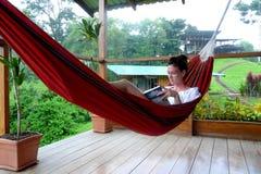 Ung kvinna som läser en bok på en hängmatta i Fincas Royaltyfri Foto