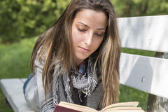 Ung kvinna som läser en bok på en parkerabänk royaltyfria bilder