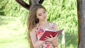 Ung kvinna som läser en bok på naturen stock video