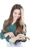 Ung kvinna som läser en bok på vit bakgrund Royaltyfri Foto