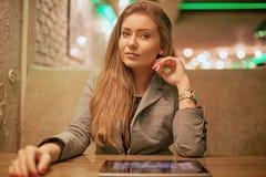 Ung kvinna som läser en digital minnestavla Arkivbild