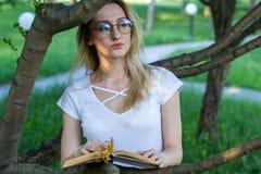 Ung kvinna som läser ett boksammanträde i buskarna på sommardagen Arkivbild