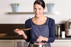 Ung kvinna som lagar mat över ugnen Arkivbild