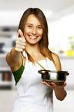 Ung kvinna som lagar mat sund mat - ok tecken Arkivbild