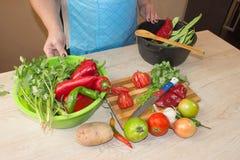 Ung kvinna som lagar mat sunt mål i köket Laga mat hemmastadd sund mat kök som förbereder grönsakkvinnan Kocken klipper th Royaltyfria Foton