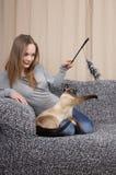 Ung kvinna som leker med katten Royaltyfri Fotografi