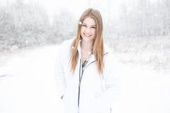 Ung kvinna som ler att stå i snö Royaltyfria Bilder