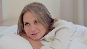 Ung kvinna som ler charminlgy ligga på en kudde lager videofilmer