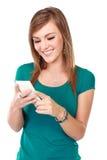 Ung kvinna som ler genom att använda mobiltelefonen Royaltyfri Fotografi