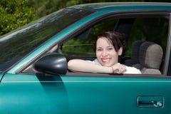 Ung kvinna som ler i förarsäte Arkivfoton