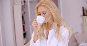 Ung kvinna som ler i nöje som tycker om kaffe Royaltyfria Bilder
