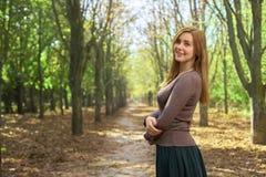 Ung kvinna som ler i parkera arkivfoto