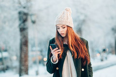 Ung kvinna som ler med den smarta telefonen och vinter Royaltyfri Foto