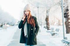 Ung kvinna som ler med den smarta telefonen och vinter Fotografering för Bildbyråer