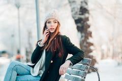 Ung kvinna som ler med den smarta telefonen och vinter Arkivbild