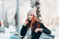 Ung kvinna som ler med den smarta telefonen och vinter Royaltyfria Bilder