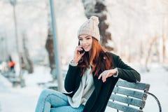 Ung kvinna som ler med den smarta telefonen och vinter Arkivbilder
