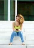 Ung kvinna som ler med hörlurar Royaltyfri Foto
