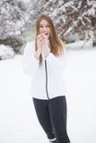Ung kvinna som ler med snöbollen Royaltyfri Fotografi