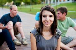 Ung kvinna som ler med vänner Arkivfoton
